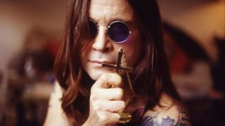 Ozzy Osbourne holds a crucifix to the camera