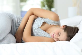 A woman lays on a bed, holding her abdomen in pain.
