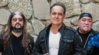 Neal Morse Mike Portnoy and Randy George standing against a wall