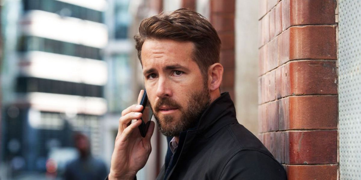 Ryan Reynolds holds a cell phone to his ear while standing against a brick wall.
