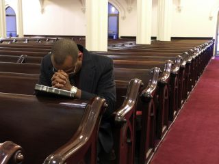 A man prays alone in church.