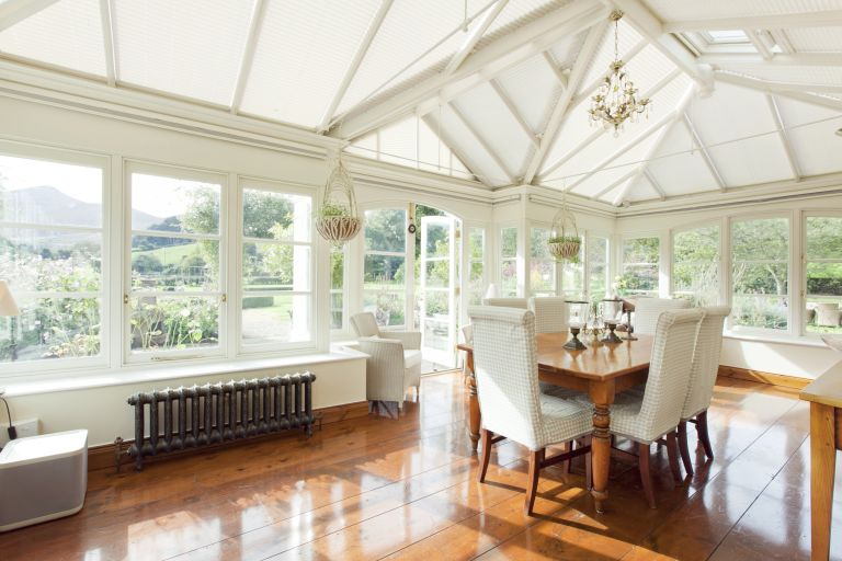 sunroom with dining table and mahogany style flooring white paint