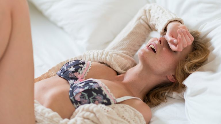 Young woman in bedroom - stock photo