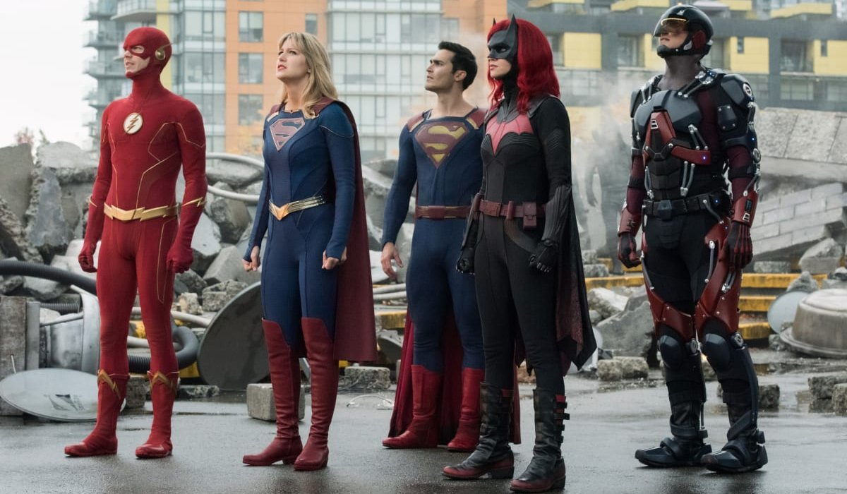 Supergirl stands with her fellow heroes amid some rubble