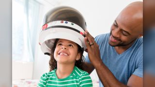A girl tries on a astronaut helmet with her dad