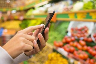 A person uses their smartphone while grocery shopping.