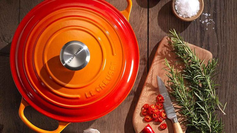 Le Creuset sale: Le Creuset Signature Enamelled Cast Iron Round Casserole Dish With Lid on side next to chopping board with rosemary and knife