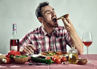 Man eating a whole pizza with wine.