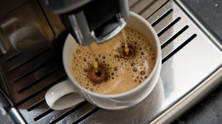 An espresso machine pouring coffee into a cup