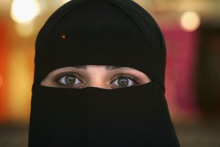 A Muslim woman wearing a Niqab poses inside a shop in the British northern town of Blackburn.