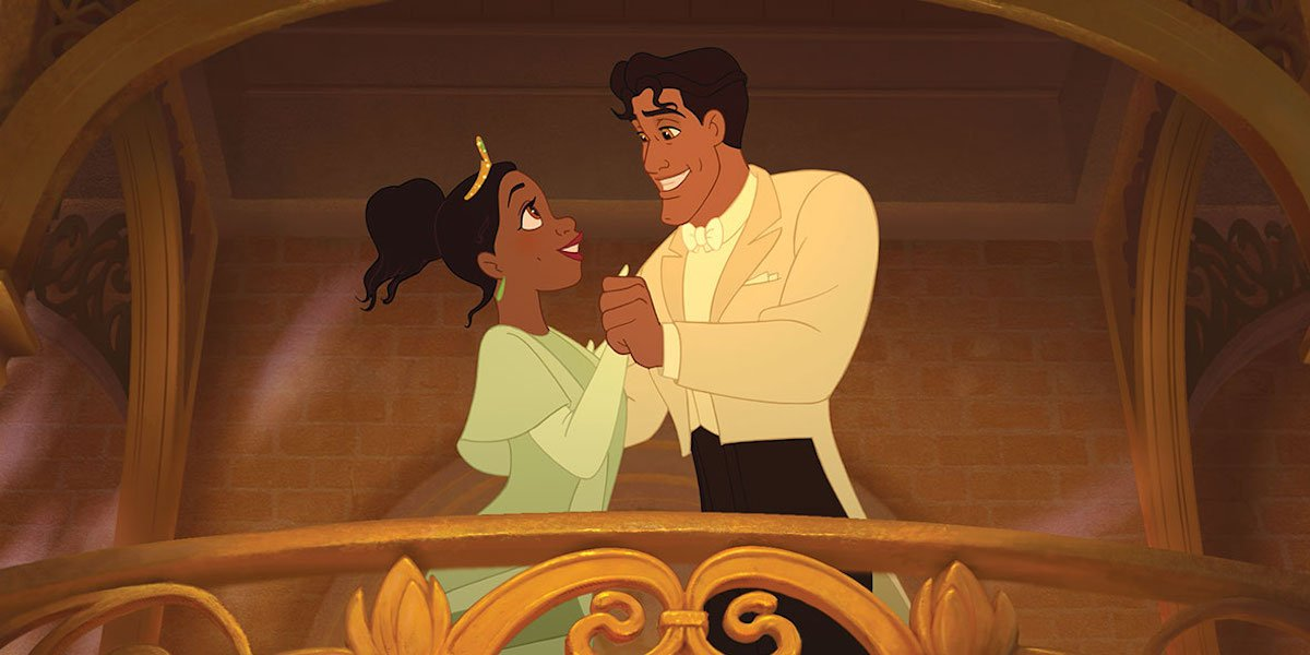 Tiana embraces Prince Naveen while standing on an ornate balcony in 'The Princess and the Frog'