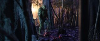 Swamp Thing looms over a decapitated body in a forest.