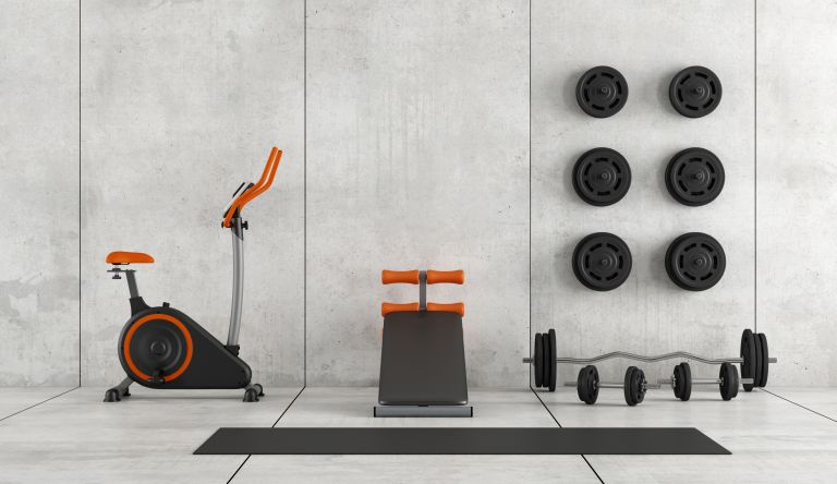 Best home gym equipment: interior of home gym with concrete walls