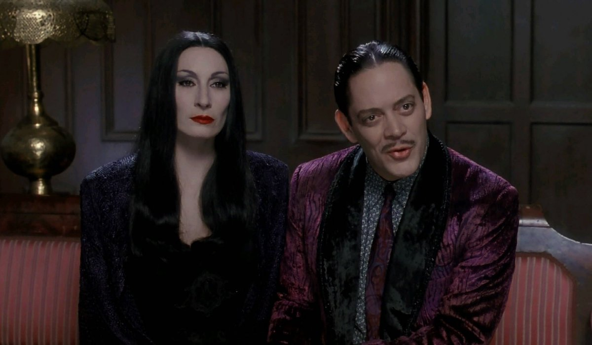 The Addams Family Anjelica Houston and Raul Julia sitting on the couch, in conversation