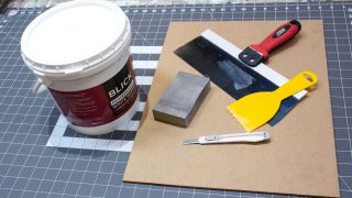A tub of gesso next to a board and scraping tools