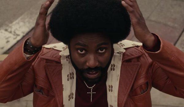 John David Washington as Ron Stalworth adjusting his afro in BlackKklansman