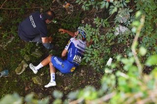 A race doctor reaches Remco Evenepoel after his crash