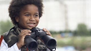 Boy holding binoculars.