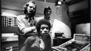 Jimi Hendrix (1942 - 1970) (seated), South African-born American music producer and engineer Eddie Kramer (standing left) and studio manager Jim Marron as they pose in the control room of Hendrix's then still under construction Electric Lady Studio, New York, New York, June 17, 1970.