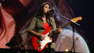 """Amy Winehouse performs on stage as part of """"The Miller Strat Pack"""" concert, at Wembley Arena on September 24, 2004 in London. The event pays homage to the Fender Stratocaster, is in aid of Nordoff-Robbins Music Therapy, and celebrates 50 years of the iconic guitar."""