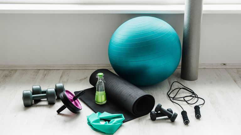 Empty modern white bright room with home workout accessories equipment.