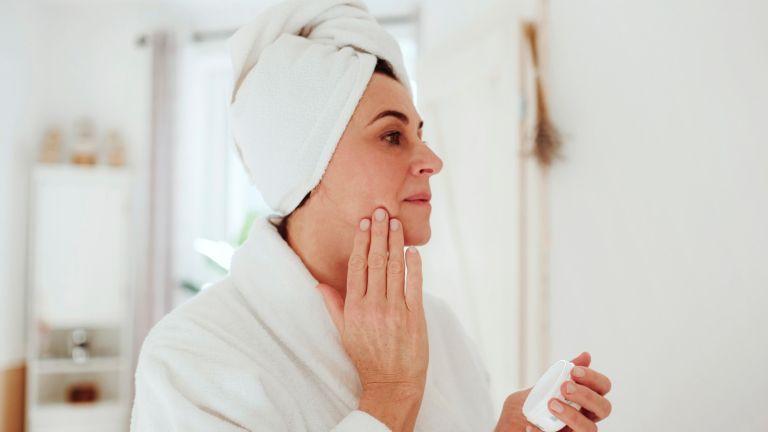 Mature woman in a bathroom at home applying dark spot serum - stock photo