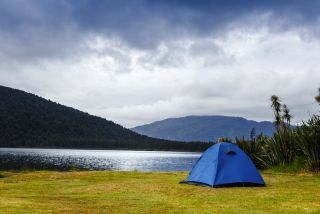 A tent is staked at the edge of a mountain lake.