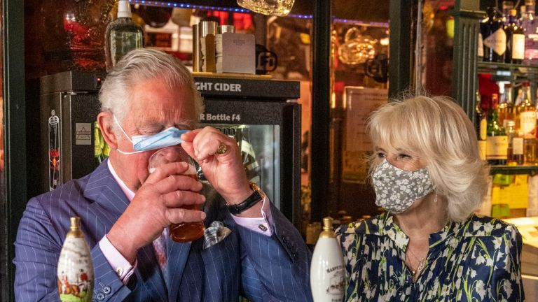 Camilla Parker Bowles showed off her witty side during a recent pub visit with Prince Charles . CLAPHAM, ENGLAND - MAY 27: Prince Charles, Prince of Wales adjusts his face mask to enable him to sip a pint that he pulled in a pub alongside Camilla, Duchess of Cornwall during a visit to Clapham Old Town on May 27, 2021 in Clapham, England. (Photo by Heathcliff O'Malley - WPA Pool/Getty Images)