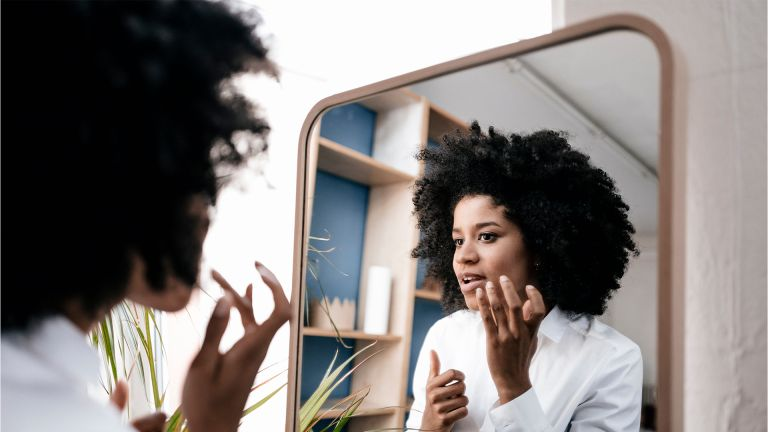 Young woman applying lip care - stock photo