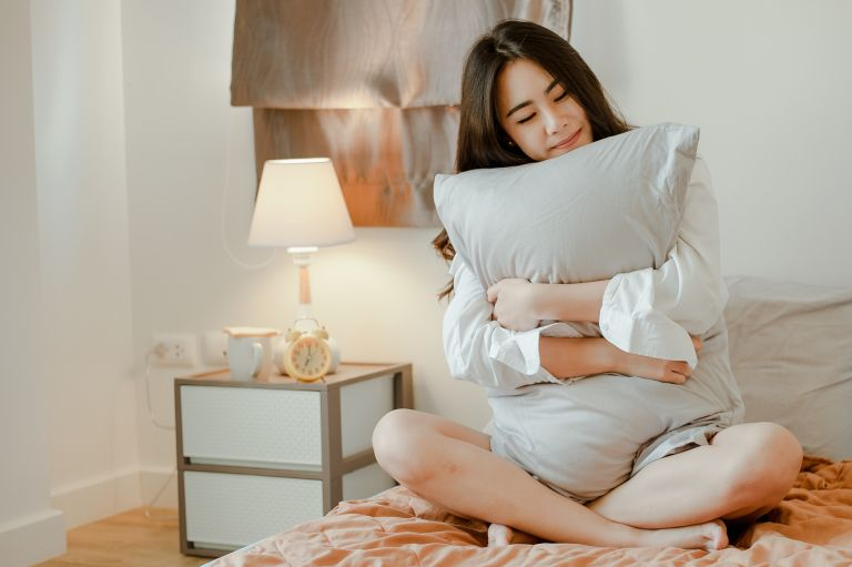 Young Woman Embracing Pillow While Sitting On Bed At Home - Best pillows for sleep
