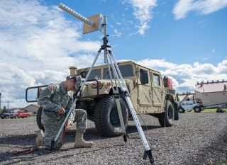 U.S. Army Spc. Angel Mendoza, assigned as a space aggressor operator to the 527th Space Aggressor Squadron, Schriever Air Force Base, Colorado, secures a helical antenna to a gravel pad Aug. 8, 2016, at Eielson Air Force Base, Alaska.