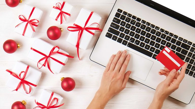 Christmas presents on side with laptop and credit card