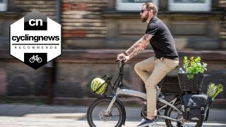 Man rides the Tern Vektron, one of the best folding electric bikes, whilst carrying plants, a pineapple and a watermelon in the on-bike storage compartments