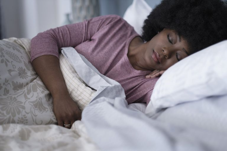 How a pillow could alleviate your pain: woman sleeping in bed with pillow
