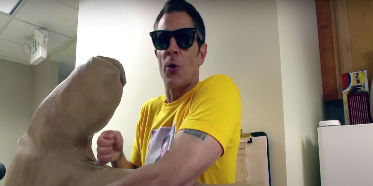 Johnny Knoxville with sunglasses on and a yellow shirt holding a giant hand and getting ready to hit the Jackass guys with it.