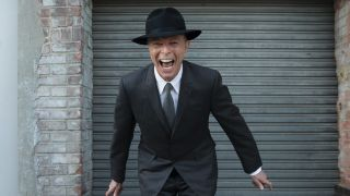 A photograph of David Bowie standing outside a metal shutter smiling in a hat, 2015
