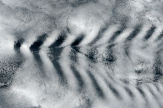 "The tall peaks of Amsterdam Island interrupted air currents passing by and created cloud ""waves."""