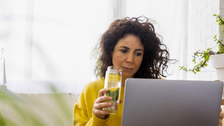 Woman drinking water at laptop