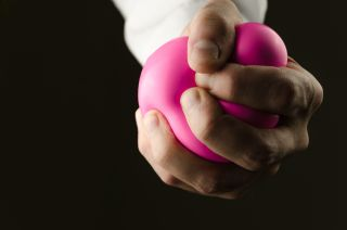 A man squeezing a stress ball.