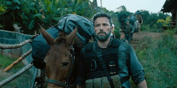 Triple Frontier Ben Affleck walking a donkey with bags of money in the jungle