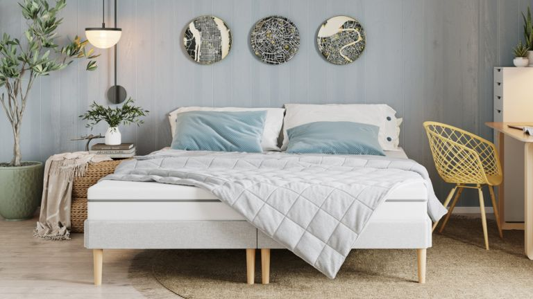 A pale grey weighted blanket laying on a bed in a contemporary bedroom