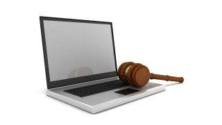 Gavel lies atop open laptop computer