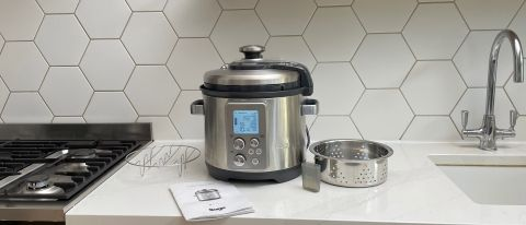 Breville the Fast Slow Pro on a kitchen countertop with its accessories laid out