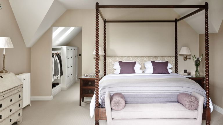 Walk-in closet ideas with white storage solutions, shown beyond a taupe colored bedroom with large four poster bed.