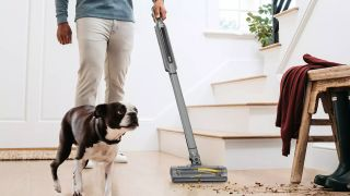 A man using the Shark WandVac to clean up spills ;on a wooden floor next to some stairs with a dog beside him