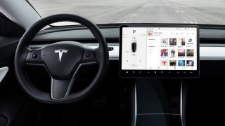 Steering wheel and central display inside the cabin of the Tesla Model 3