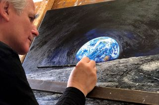 """Chris Calle puts the finishing touches on """"Touched by the Moon,"""" his moon tree-dust infused tribute painting for the 50th anniversary of NASA's Apollo 14 moon landing mission."""
