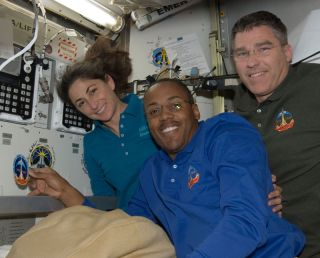 Space shuttle Discovery astronauts Alvin Drew, center, Nicole Stott and Steve Bowen add their mission patch as designed by the late, famed space artist Robert McCall to the International Space Station's wall.