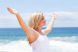 A woman walks on a beach with her arms raised and outstretched