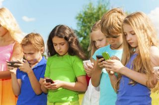 Group of kids on a summer day looking at their cell phones